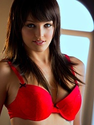 Macy Cartel sits on a red bed - Digital Desire